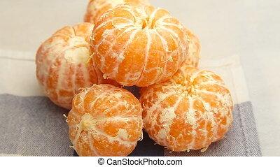 peeled tangerines rotate - Orange slices rotating on a...