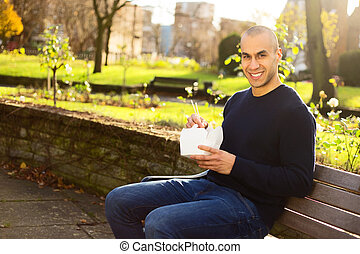 take away lunch - young man enjoying a take-away in the park
