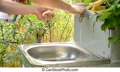 Washing hands at simple vanity unit outdoors - Closeup of...