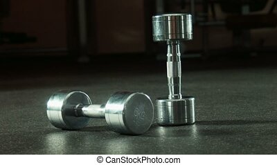 two dumbbells in gym wide shot