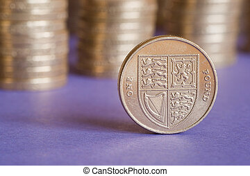 British pound - One pound coin in front of stacks of several...