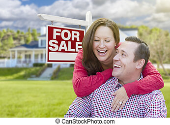 Happy Couple In Front of For Sale Sign and House