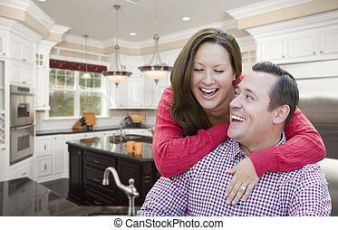 Happy Laughing Couple In Beautiful New Kitchen