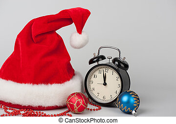 Christmas still life. Santa hat, decorations and clock