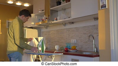 Adult Man Ironing White Shirt In The Kitchen - Caucasian...
