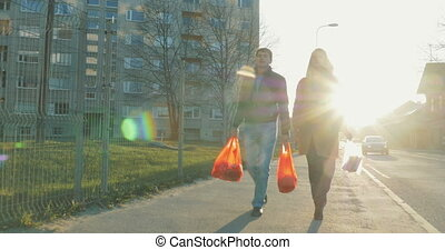Couple with bags going home after shopping - Steadicam shot...