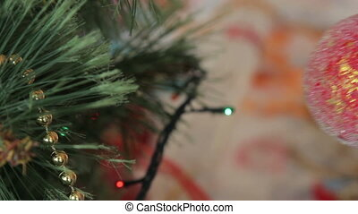 girl hanging decorative toy ball on Christmas tree
