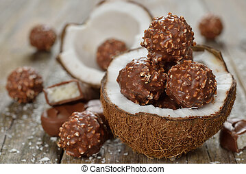 Chocolate praline and coconut on a wooden background
