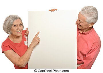 Old couple with board - Two elderly posing with board on...