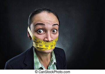 Silent woman - Businesswoman with tape ruler round her face...