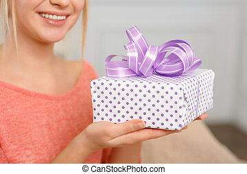 Young smiling woman holding a wrapped present - Check it out...