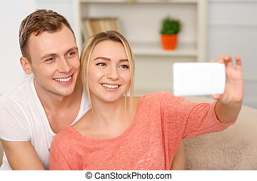 Young happy couple is busy taking selfie. - Couples selfie....