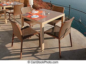 outdoor cafe on terrace over sea coast, Santorini - empty...