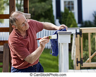 Painting fence - Senior man painting a wooden decking fence