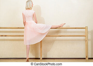 Young woman stretching in dancing classroom.