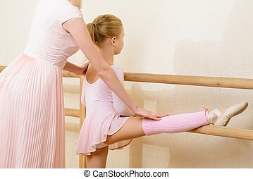 Teacher helping her apprentice to stretch up