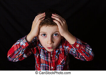 Confused little boy with hand on his head