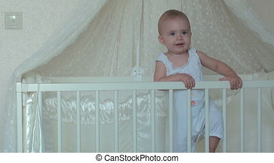 Cute little baby girl standing on the bed - Portrait of a...