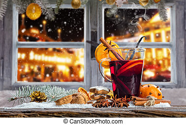 Hot red wine drink on wooden table with old window overlook...