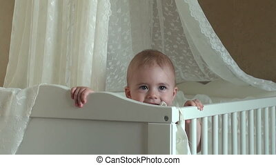 beautiful little girl playing in a crib and smiling.