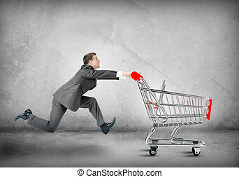 Businessman pushing shopping cart on grey wall background