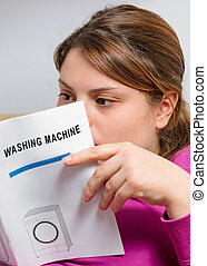 booklet of washing machine - housewife reads instruction...