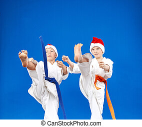 High kick in perfoming athletes in caps of Santa Claus
