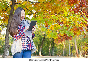 woman with tablet in autumn