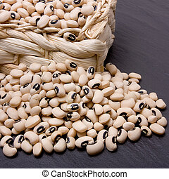 Black eyed peas overflowing from wicker basket against dark...