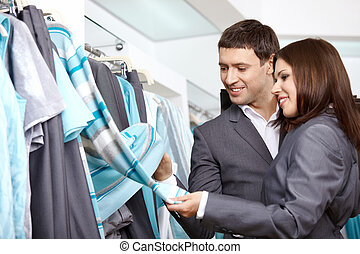 Showroom - The young couple considers clothes in shop