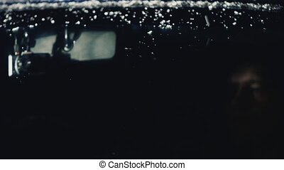 The man behind the glass of the car under snowing - A man...