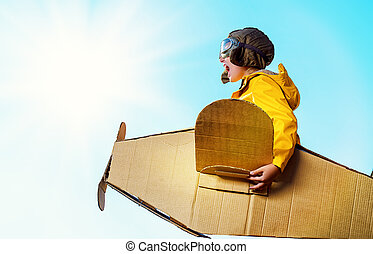 imagination - Eight-year boy playing with a cardboard...