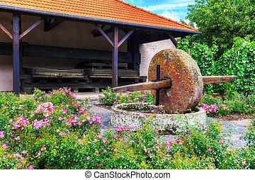 Summer garden with ancient wine press
