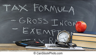 Desktop and chalkboard for learning how to do income taxes...