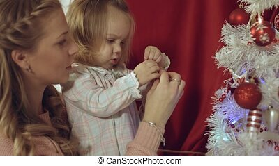 Mum with a small daughter decorate a Christmas tree