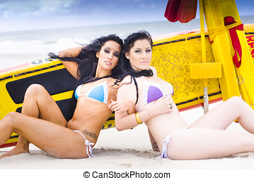 Beach Babes - Two Surfer Beach Babes Lie Back To Back In...