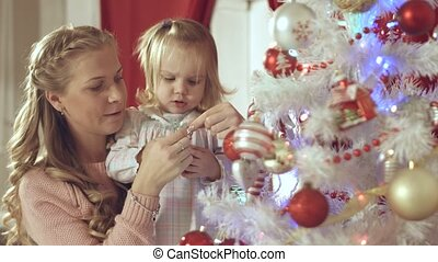 Mother with adorable baby decorate a Christmas tree at home...