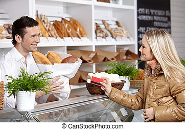 The girl and the seller - The young girl buys bread in shop