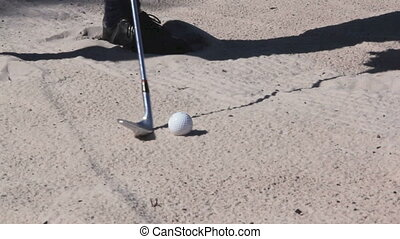 Golf 4 - A golf ball is chipped out of a sand bunker by a...