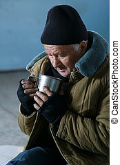 Homeless man holding his iron cup - Beggar and cup Sad...