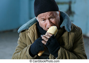Depressed senior-aged beggar eating bread - Hungry man Upset...