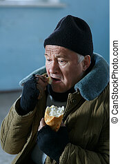 Depressed senior-aged beggar eating bread - Poor food...