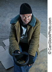 Senior-aged old bum is holding his tip cap.