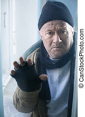 Homeless man looks out of the window - Scared and unhappy...