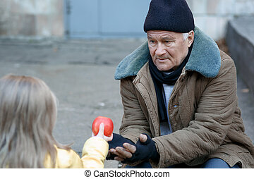 Little girl gives apple to the beggar. - Getting food. Kind...
