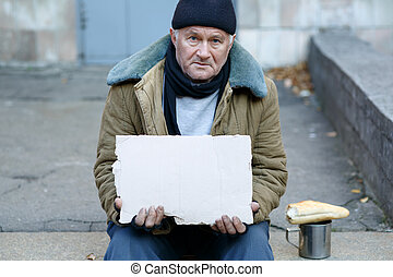 Homeless man holding a cardboard sign - Seeking help Sad...