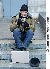 Homeless man holding his iron cup - Beggar on streets Sad...