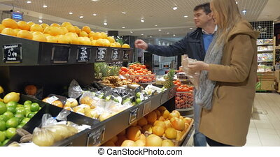 Happy Couple Choosing Oranges In Supermarket