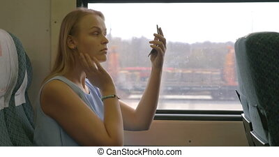 Young woman putting make-up in train
