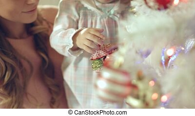 Little girl playing with Christmas toy near the Christmas tree with mother